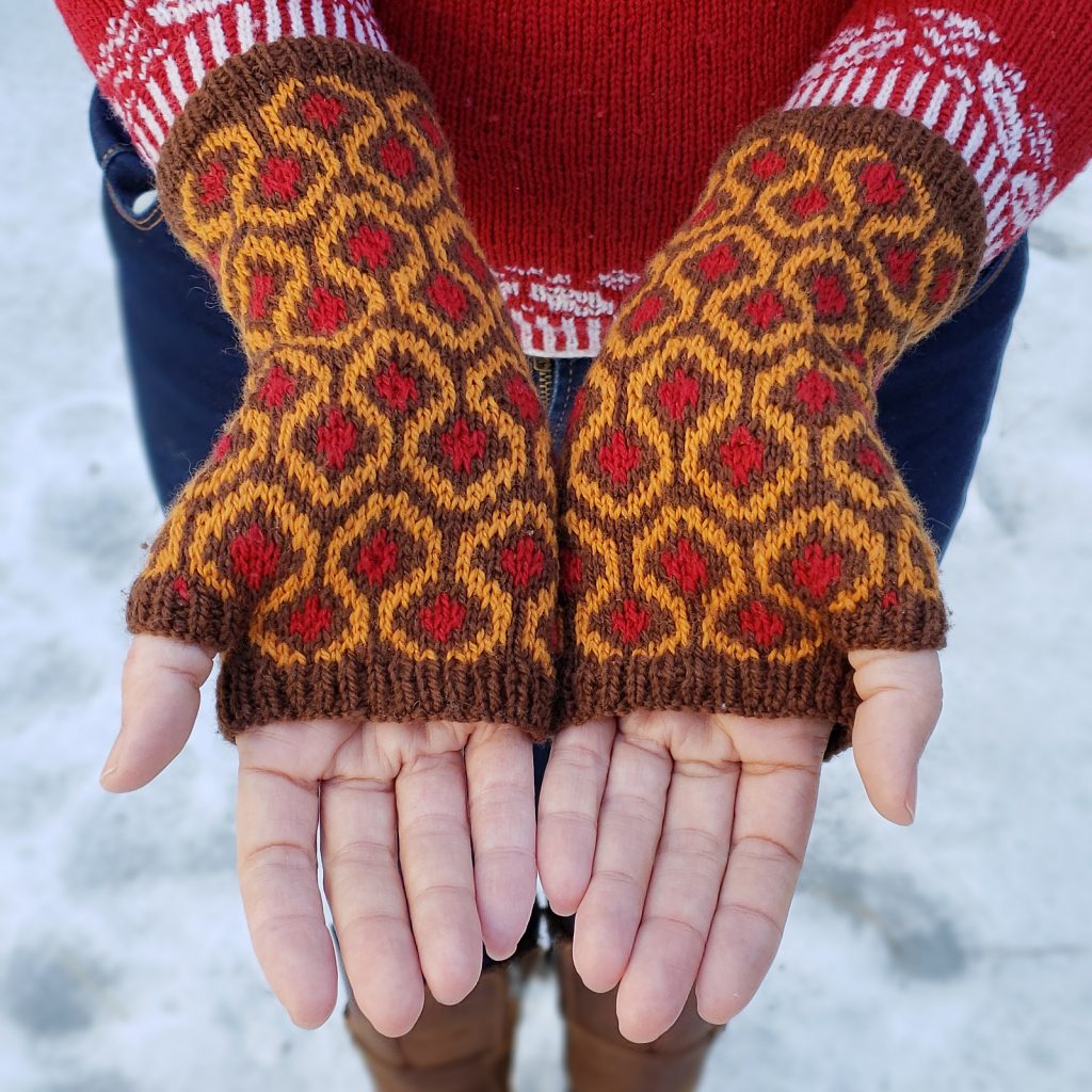 A pair of hands showing open palms while wearing mitts featuring the pattern from the famous carpet in THE SHINING.