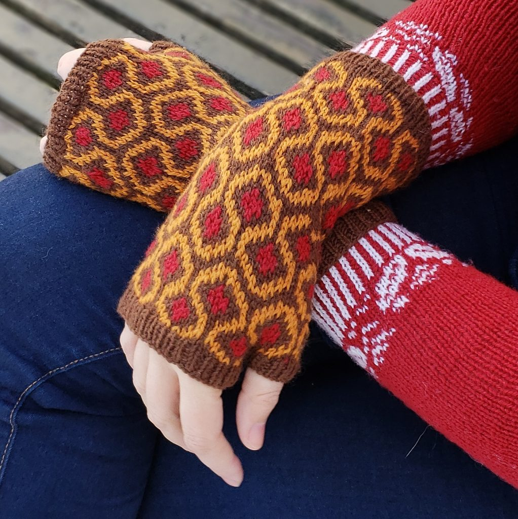 A pair of hands crossed at the wrist while wearing mitts featuring the pattern from the famous carpet in THE SHINING.