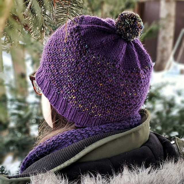 A woman wearing a purple version of this hat pattern.