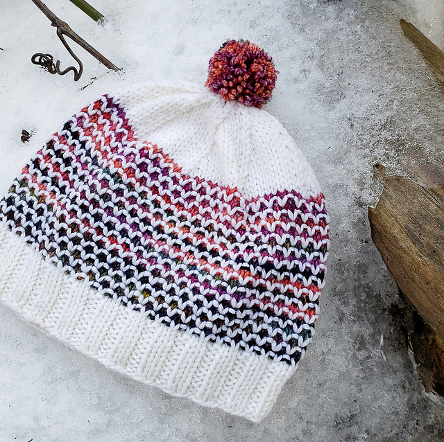 A white toque featuring a pink and purple broken seed stitch motif laying flat in the snow.