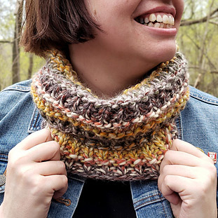 A woman wearing a chunky, multi-coloured, textured cowl.