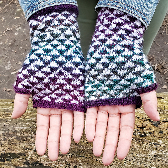 A pair of palms outstretched wearing a pair of mitts featuring a triangle motif.