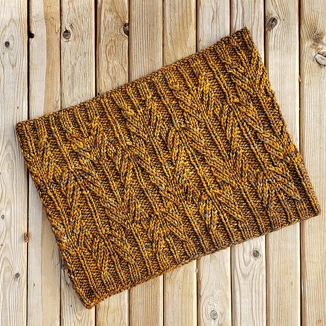 A brown cabled cowl laid flat on a wood boardwalk.