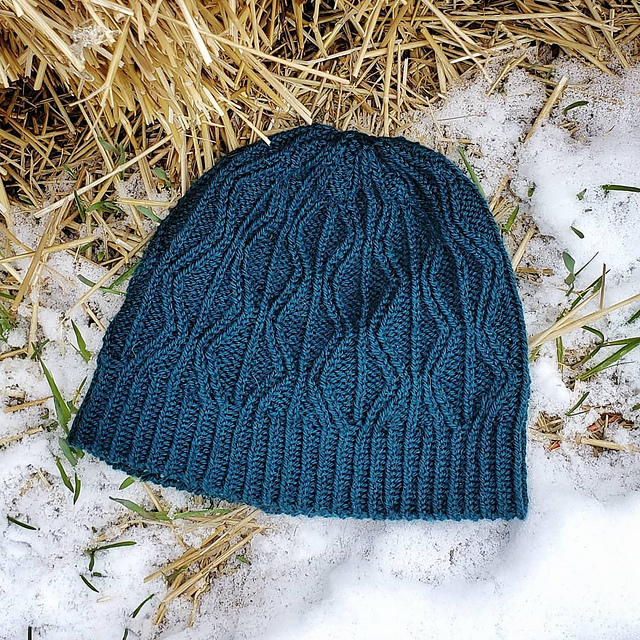 Blue hat with geometric diamond-shaped cables laid flat in the snow