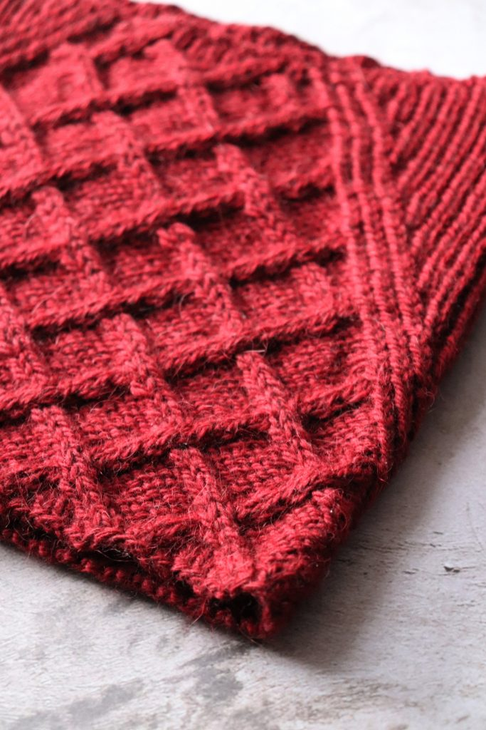A red cabled cowl laid flat.