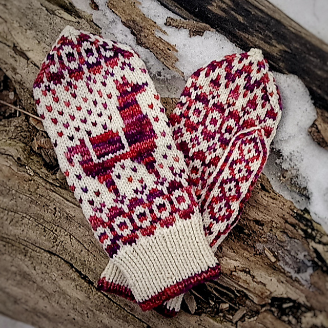 A pair of burgundy and white mittens with llamas on them.