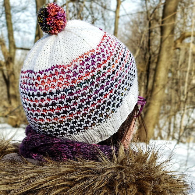 View of a winter hat from behind. Hat features an all over fish-scale type pattern.