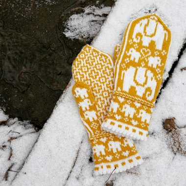 Yellow and white mittens featuring a white elephant on the front and a geometric motif on the palm.