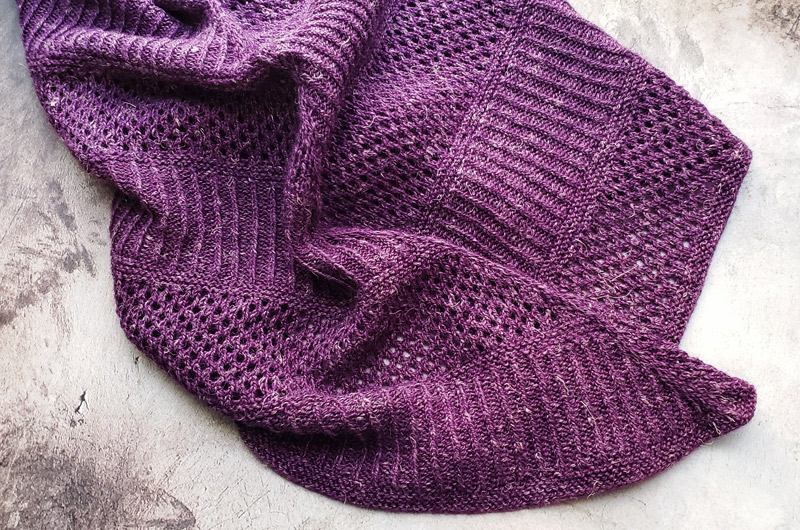 A purple cowl with alternating bands of ribbing and lace laid flat on a concrete surface.