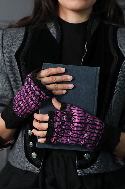 A woman holds a book while wearing a pair of mitts.