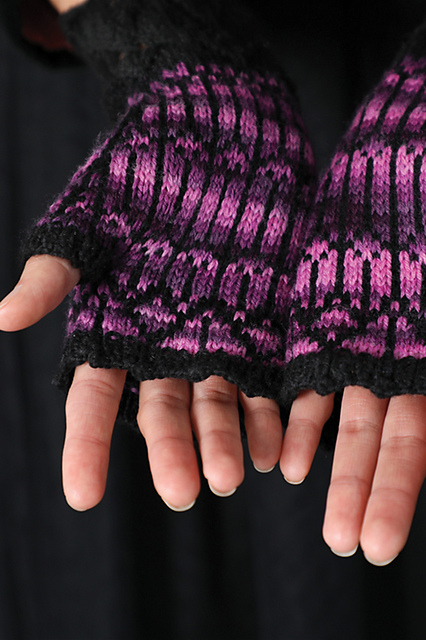 A pair of hands, palm facing up, wearing a pair of mitts.